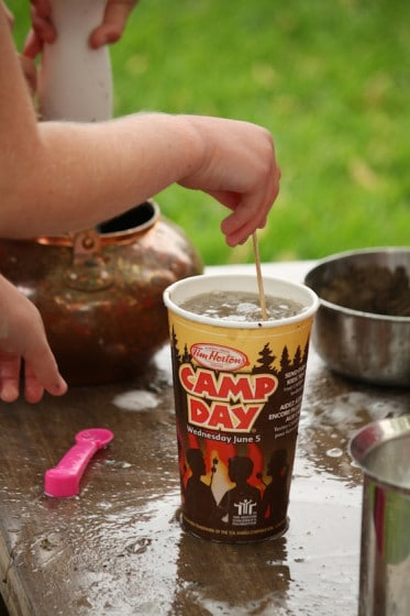 preschooler stirring water and sand in take out coffee cup