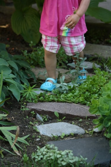 toddler walking and balancing on stepping stones