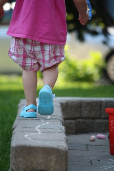 toddler balancing on low brick wall