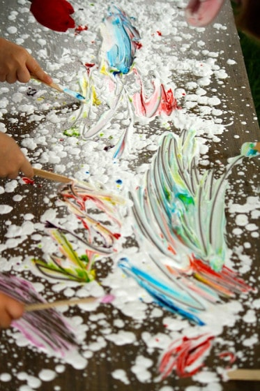 shaving cream, food colouring and craft sticks on a table top