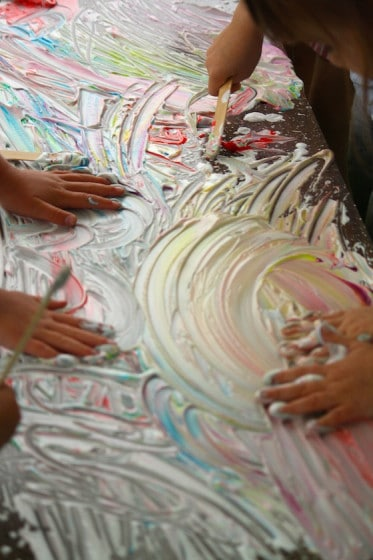 kids making art in coloured shaving cream with hands