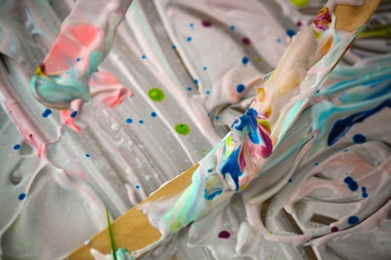 close up popsicle stick covered with shaving cream and food colouring