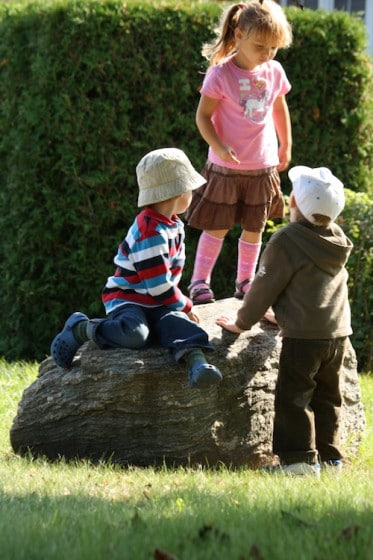 preschoolers balancing on large rock outdoors