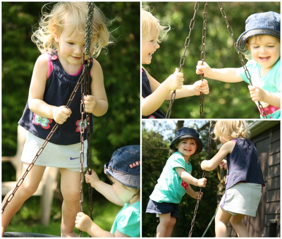 toddlers standing and balancing on the tire swing