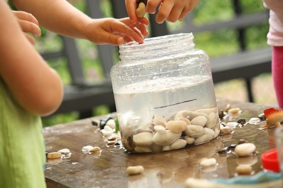 kids dropping stones into the container to raise the water level