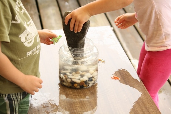 adding the largest rocks to the container in a science activity