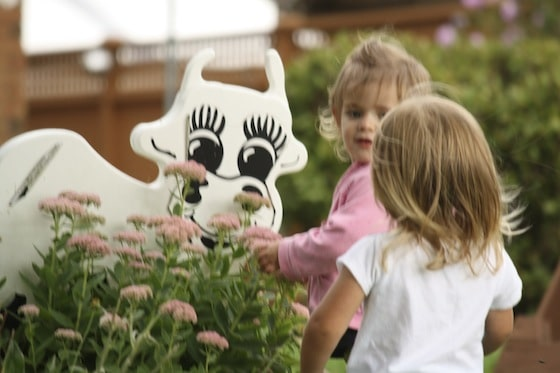 children petting a cow structure in the garden