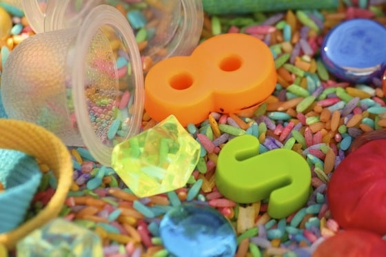 small items and coloured rice in a sensory bin
