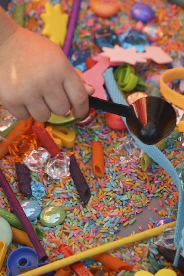 Preschooler scooping coloured rice in a sensory bin filled with assorted colourful items