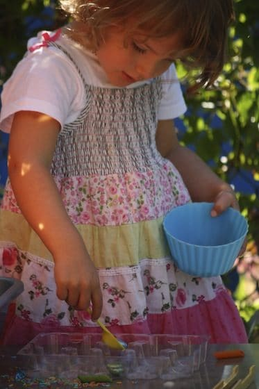 preschooler scooping beads from bowl to tray