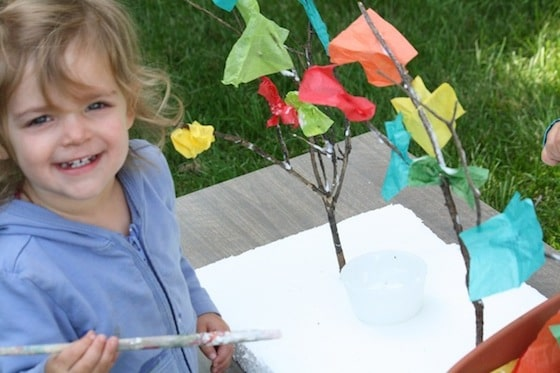 toddler making a fall tree with twigs and tissue paper