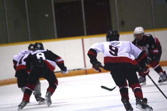 hockey players skating up the ice