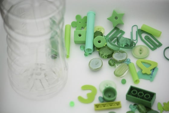 Clear bottle and green odds and ends on a styrofoam tray