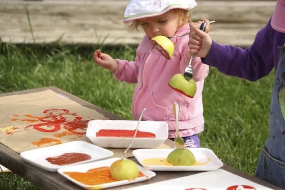 children stamping with forks stuck into apples
