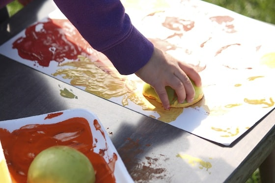 child stamping with apples