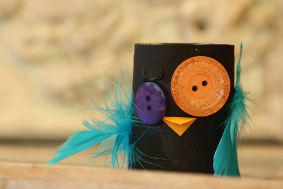 black toilet roll owl with orange and purple eyes