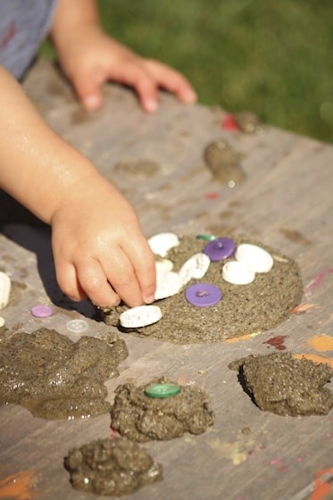 pressing buttons into a mud pie
