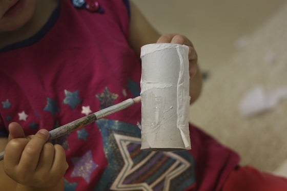 toddler painting glue on toilet roll