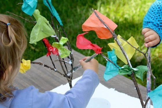 kids sticking tissue paper to twigs