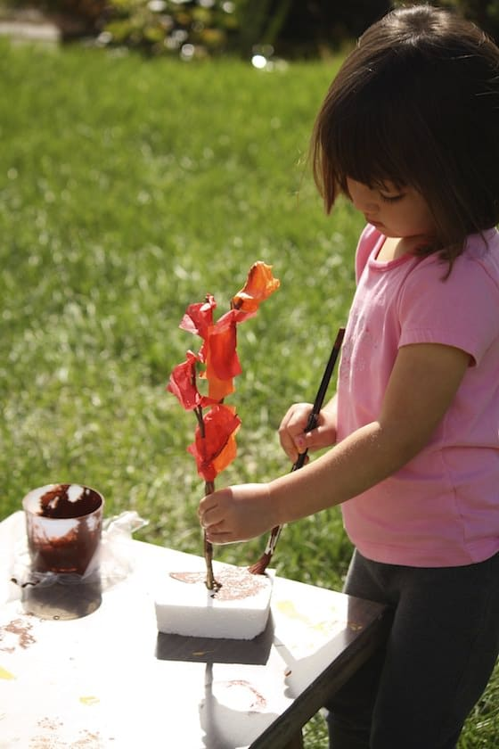 preschooler gluing red tissue paper to twig