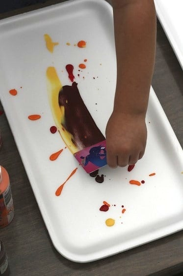 preschooler spreading paint with credit card