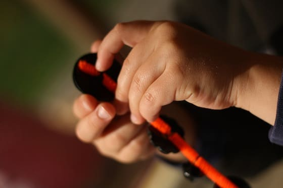 Child threading black buttons onto orange pipe cleaner