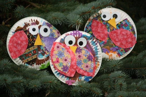 3 paper plate owls hanging in pine tree