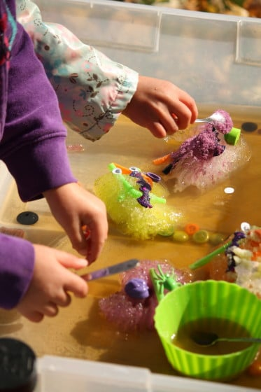 kids melting frozen ice-hands with coloured salt and water