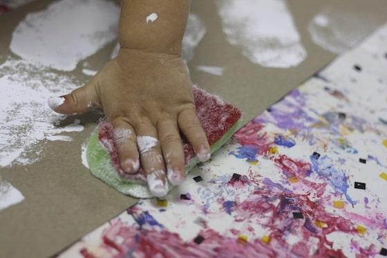 toddler hand pressing painted sponge on cardboard