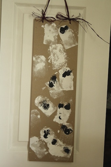 stamped ghost art hanging on door