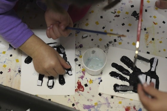 "gluing styrofoam ""bones"" onto hands for an x-ray craft"