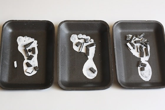 3 white painted footprints on styrofoam meat trays