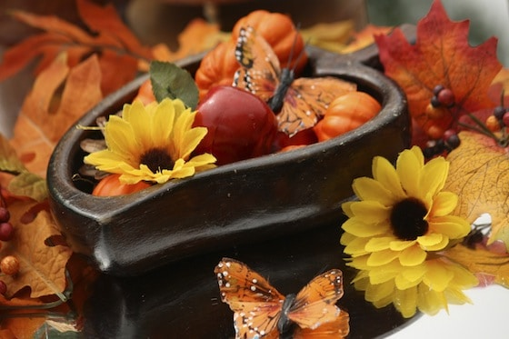 Wooden bowl filled with artificial sunflowers, pumpkins and apples on a mirrored fall sensory table