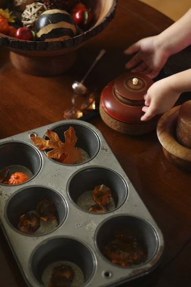 sorting fall items into bowls and a muffin tin at the Fall Sensory Table