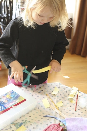 preschooler cutting strips of paper