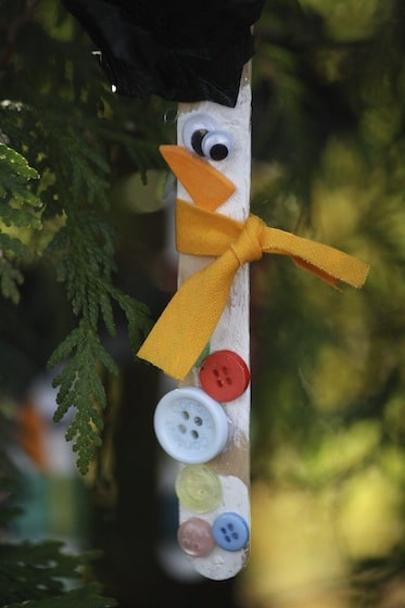 Popsicle stick snowman ornament hanging in christmas tree