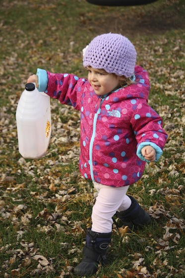 toddler carrying milk jug bird feeder to the back of the yard
