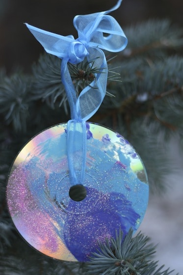 painted and glittered cd christmas ornament hanging in tree