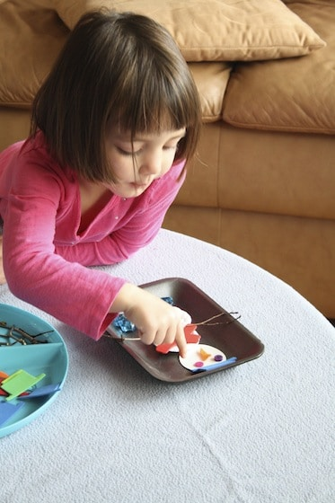 child building a snowman on a table top with craft scraps