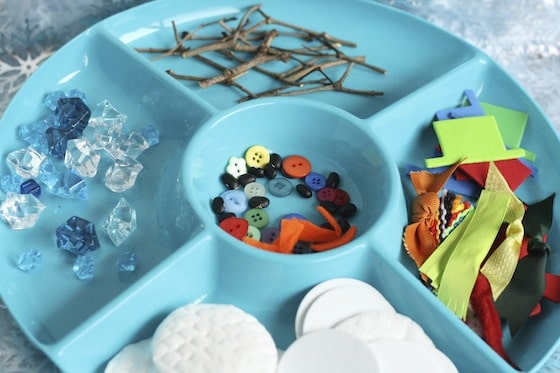 snowman building activity tray filled with supplies