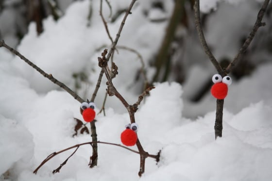 small twig reindeer decorations stuck into the snow