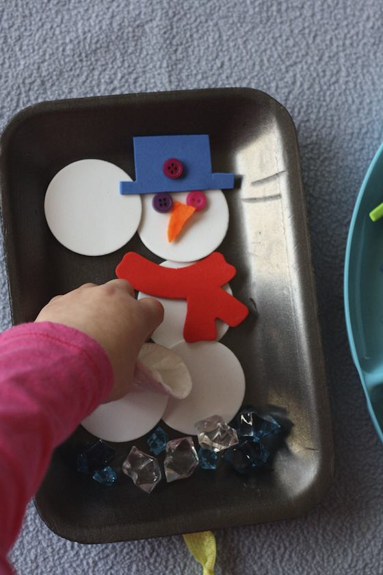 child building snowman with craft supplies