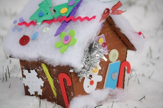 decorated cardboard gingerbread house sitting on snowy ground