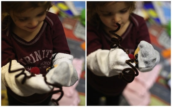 child playing with homemade christmas sock puppets