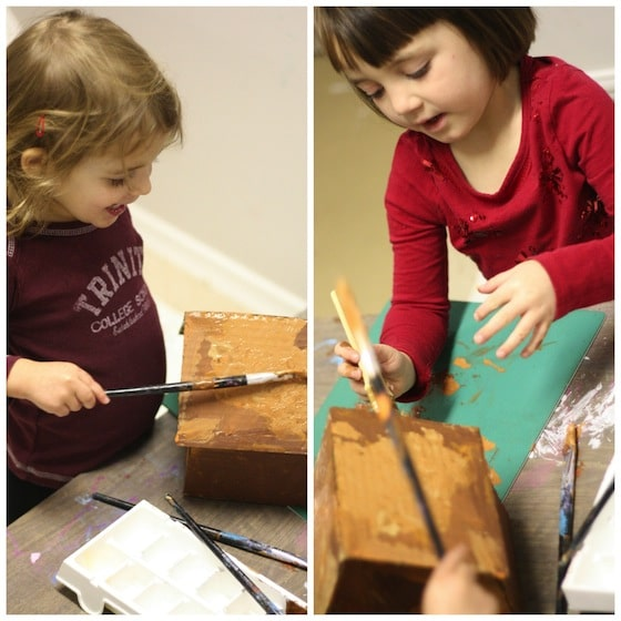 toddlers painting cardboard house brown