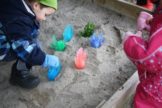 children discovering icy hands in sandbox