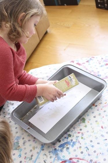 child pours salt over glue letters