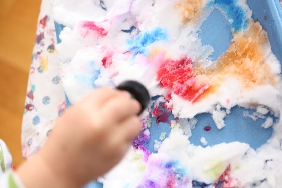 toddler uses liquid watercolours to colour the snow