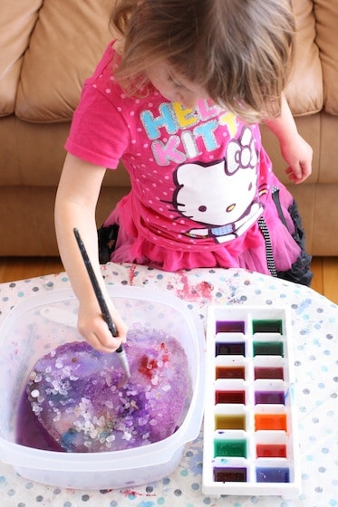 preschooler painting an ice heart with rock salt and watercolours