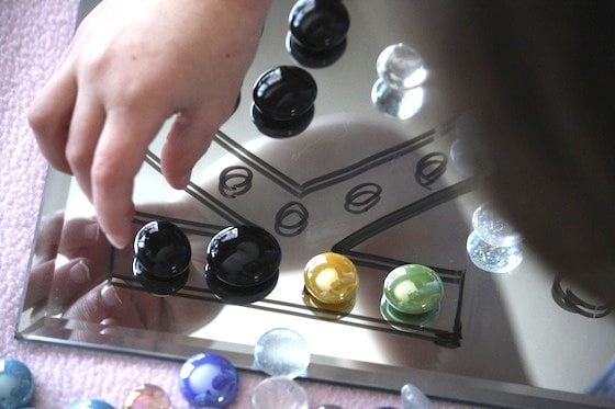 placing glass beads on a drawing on a mirror